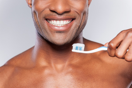 Man with tooth brush. Cropped image of young shirtless African man holding a toothbrush with toothpaste and smiling while standing against grey background photo