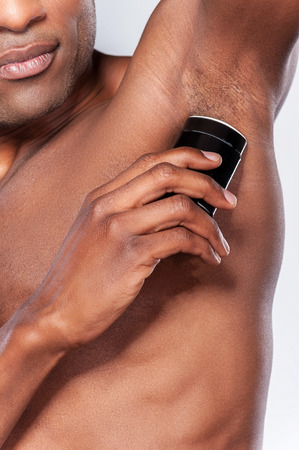Staying clean and fresh. Cropped image of young shirtless African man using dry deodorant while standing against grey background photo