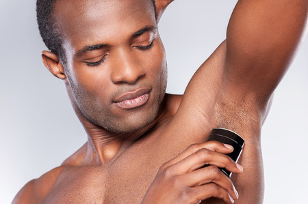 Always clean and fresh. Young shirtless African man using dry deodorant while standing against grey background photo