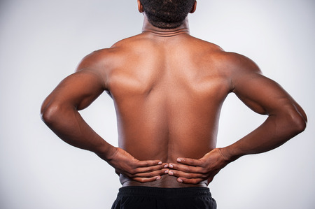 Backache. Rear view of young muscular African man touching his hip while standing against grey background photo