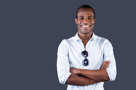 facial muscles: Charming handsome. Handsome young black man in blue shirt keeping arms crossed and smiling at camera while standing against grey background Stock Photo
