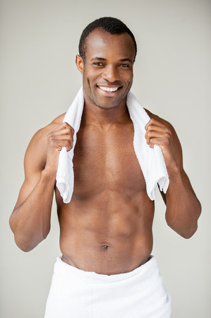 Just after shower. Handsome young African man wrapped in towel looking at camera and smiling while standing isolated on white background photo