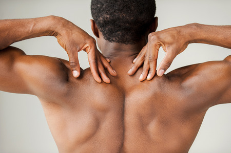 Muscular black man. Rear view of young muscular black man touching his shoulders while standing isolated on grey background photo