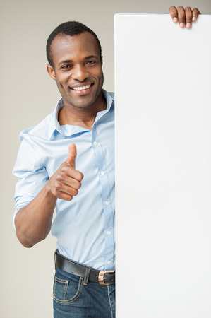 Presenting your product. Cheerful African man in blue shirt leaning at copy space and showing his thumb up while standing against grey background photo