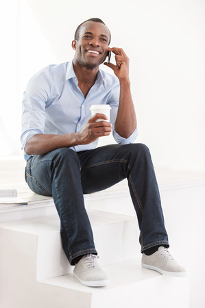 of african descent: Good talk. Cheerful young African man in blue shirt holding a cup of coffee and talking on the mobile phone Stock Photo
