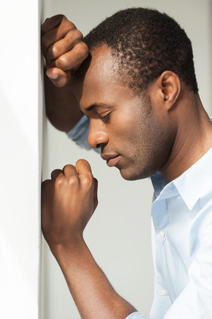 Depression and hopelessness. Side view of depressed young African man in blue shirt leaning at the wall and keeping eyes closed photo