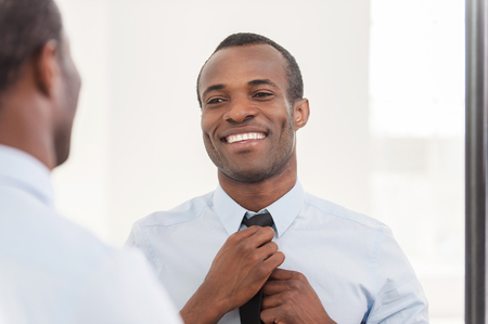 adjusting: Confident about his look. Young African man adjusting his necktie while standing against mirror