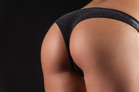 female buttocks: Perfect bum. Close up image of perfect female buttocks against black background