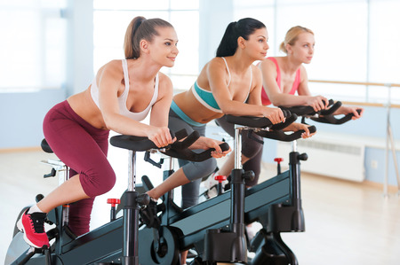 Cycling on exercise bikes. Two attractive young women in sports clothing exercising on gym bicycles photo