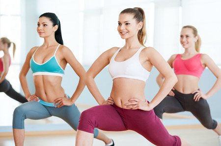 Girls on aerobics class. Three beautiful young women in sports clothing exercising together and smiling photo