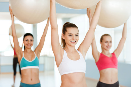 Exercising with fitness balls. Three beautiful young women in sports clothing exercising with fitness balls and smiling photo