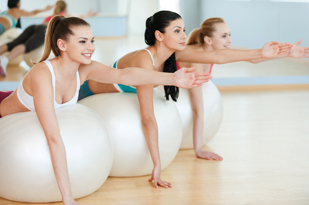 Training with fitness balls. Three beautiful young women in sports clothing exercising on fitness balls and smiling photo