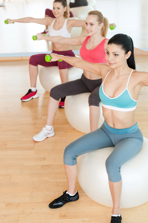 Women training with dumbbells. Top view of three beautiful young women in sports clothing holding dumbbells while sitting on the fitness ball photo