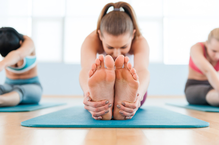 warming up: Stretching exercise. Three beautiful young women in sports clothing stretching while sitting on exercise mats