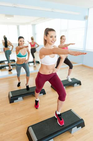 Step aerobics. Top view of three attractive young women in sports clothing doing step aerobics together and smiling  photo
