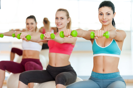 Keeping their bodies in shape. Three beautiful young women in sports clothing holding dumbbells and smiling at camera while sitting on the fitness ball photo
