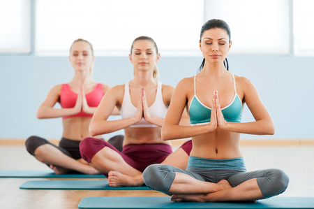 Meditating together. Three beautiful young women in sports clothing holding hands clasped and keeping eyes closed while sitting at lotus position photo