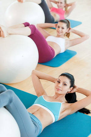 Preparing bodies for summer season. Top view of three beautiful young women in sports clothing exercising with fitness ball while lying on exercise mats and looking at camera photo