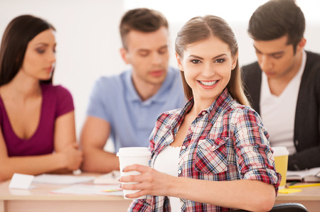 Feeling confident about her final exam. Four cheerful students sitting together at the desk and studying while beautiful woman looking over shoulder and smiling photo
