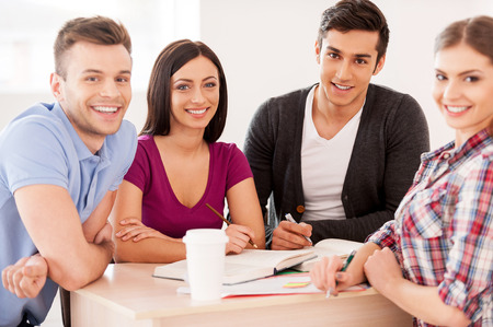 indian college student: Students studying together. Four cheerful students studying sitting at the desk together and smiling at camera