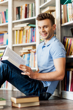 Student in library. Side view of handsome young man holding a book and smiling at camera while sitting on the floor and leaning at the library bookshelf  photo