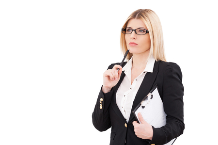 Looking for solution. Thoughtful mature businesswoman holding clipboard and touching her chin with pen while standing isolated on white photo