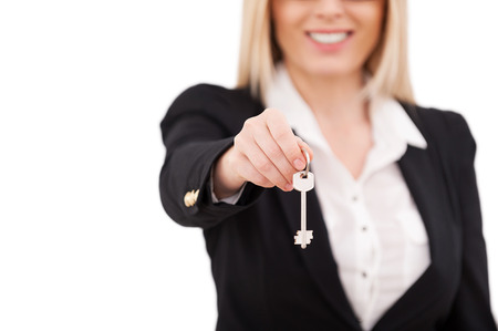Here is your key! Cropped image of mature businesswoman stretching out key and smiling while standing isolated on white photo