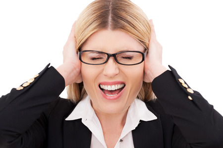 eye's closed: Emotional stress. Depressed mature businesswoman keeping eyes closed and covering ears with hands while standing isolated on white