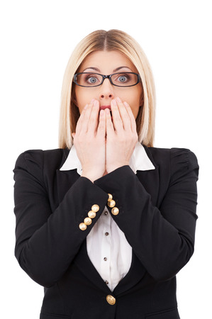 Shocked businesswoman. Shocked mature businesswoman covering mouth with hands and looking at camera while standing isolated on white photo