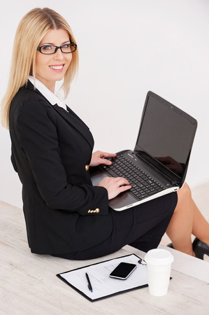 Busy and confident. Top view of confident mature businesswoman looking over shoulder and smiling while sitting at the staircase and working on laptop photo
