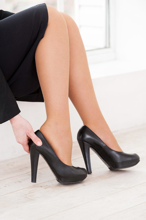 Tired legs. Close-up of woman in formalwear adjusting her high heeled shoe while sitting on the windowsill  photo