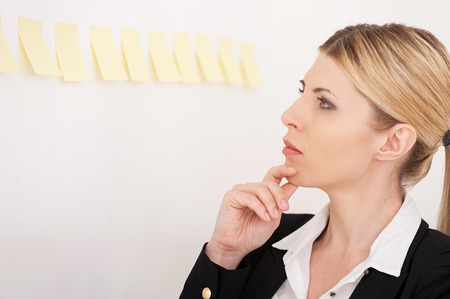 Planning her work. Side view of confident mature businesswoman pointing the adhesive notes attached to the wall photo