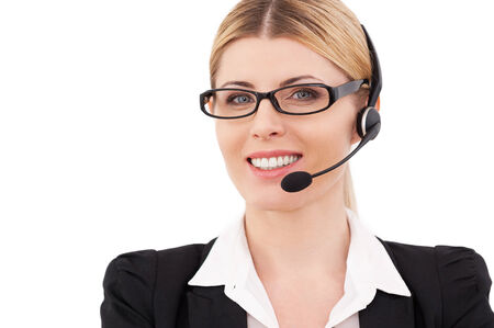 Always ready to help you. Confident mature customer service representative in headset looking at camera and smiling while standing isolated on white photo