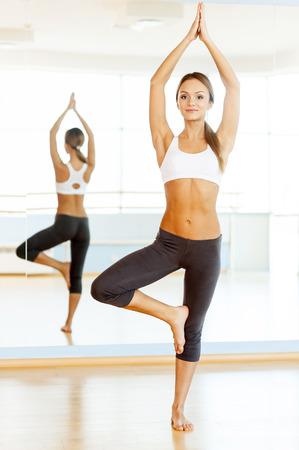 Woman exercising. Full length of beautiful young woman training in aerobics class photo