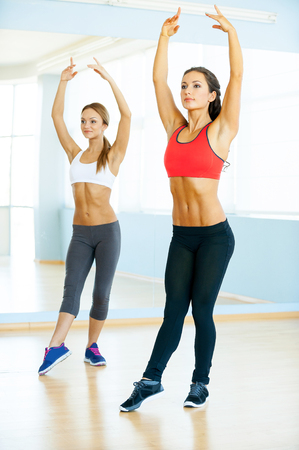 Aerobics class. Two beautiful young women in sports clothing exercising together and smiling photo