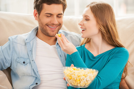 eating popcorn: Couple eating popcorn. Beautiful young couple sitting on the couch together and watching TV