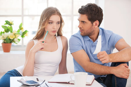 You spend too much money. Angry young man showing a bill to his wife while both sitting on the floor at his apartment photo