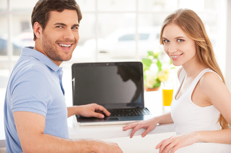 Surfing the net together. Handsome young man sitting at the table and using laptop while his girlfriend standing behind him  photo