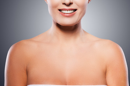 Natural beauty  Portrait of shirtless mature woman smiling while standing against grey background photo