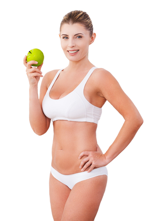 Join a healthy lifestyle  Beautiful mature woman in underwear holding a green apple and smiling while standing isolated on white photo