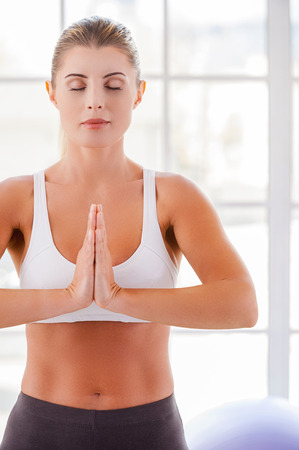 Woman mediating. Attractive mature woman mediating while keeping hands clasped photo