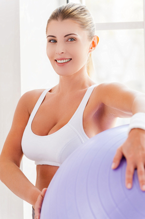 Woman with fitness ball. Attractive mature woman holding fitness ball and smiling at camera  photo
