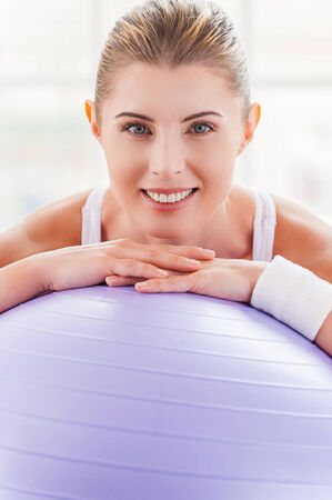 Woman with exercise ball. Beautiful mature woman leaning at fitness ball and smiling photo