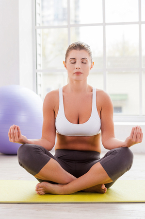 staying: Staying calm. Beautiful mature woman mediating while sitting in lotus position