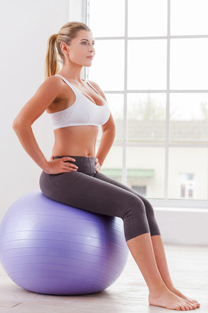 Exercising with fitness ball. Side view of mature woman sitting on fitness ball and looking away  photo