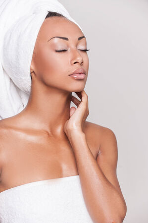 Pure beauty. Beautiful young Afro-American woman wrapped in towel keeping eyes closed and touching her face while standing against gray background photo