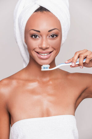 Teeth care. Portrait of beautiful young Afro-American woman holding a toothbrush and looking at camera while standing against gray background photo