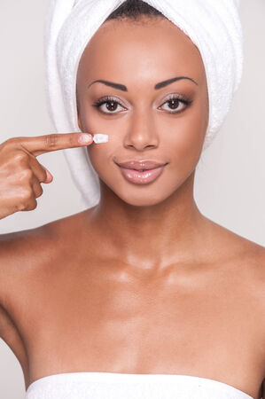 Staying young and beautiful. Close Up image of attractive young Afro-American woman spreading cream on her face and looking at camera while standing against gray  photo