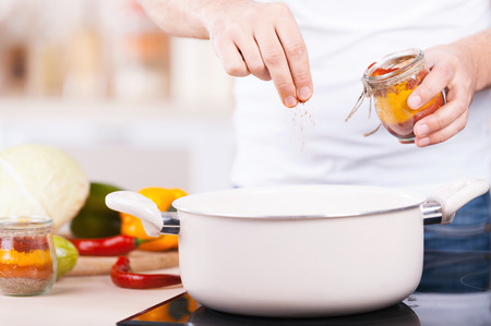 And some seasonings? Cropped image of man putting spices into a pan while standing in the kitchen