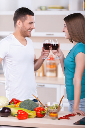 Cheers! Beautiful young couple holding glasses with red wine and looking at each other while standing in the kitchen photo